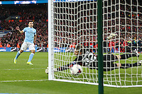 Sergio Aguero of Manchester City watches his penalty beat Simon Mignolet of Liverpool in a penalty shoot out during the Capital One Cup match between Liverpool and Manchester City at Wembley Stadium, London, England on 28 February 2016. Photo by David Horn / PRiME Media Images.