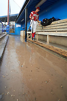 Batavia Muckdogs catcher Blake Anderson (26) walks on the dugout step as the dugout floods during a game against the Mahoning Valley Scrappers on July 1, 2015 at Dwyer Stadium in Batavia, New York.  The game was called after four pitches because of rain.  (Mike Janes/Four Seam Images)