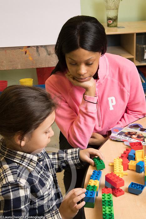 Education Preschool 4 year olds female teacher watching boy line up colored plastic bricks