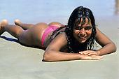 Bahia, Brazil. Smiling girl in pink bikini lying on the beach.