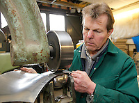 Adrian Rice, panel beater, working on the resoration of a Jaguar XK 120.  First he builds a wooden formwork then makes new aluminium panels to fit it.  Here using a Ranalah Wheeling machine.  Once the panels are fixed in position, the wooden formwork is removed.