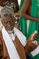 Village Imam and Cell Phone at Djilor, a Wolof Village, near Kaolack, Senegal. DOZENS MORE OF IMAGES RELATED TO MILLET CULTIVATION ARE AVAILABLE.  WHAT DO YOU NEED?