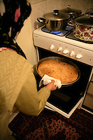 Turkish woman taking cornflour bread (misir ekmek) out of the oven, Turkey