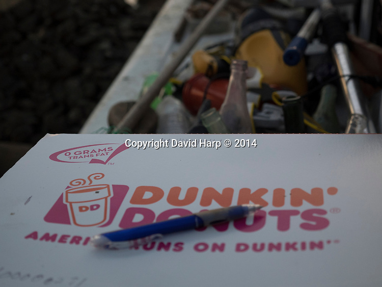 Captain Wadey Murphy, Jr. uses a Dunkin Donuts box, which was full when they started dredging at sunrise, to tally bushels of oysters being offloaded at Long Wharf in Cambridge.