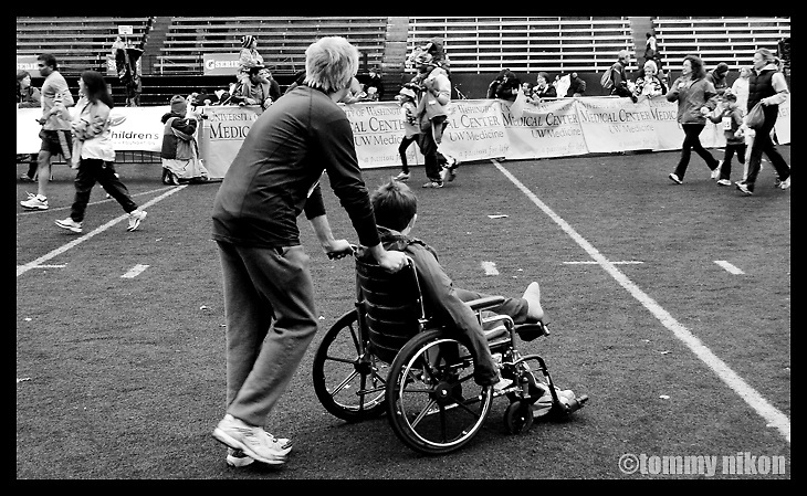 A father pushing his injured son to the finish line of a fun-run sponsored by Children's Hospital.  He was injured prior to the race, but still wanted to see the finish...and finishers.