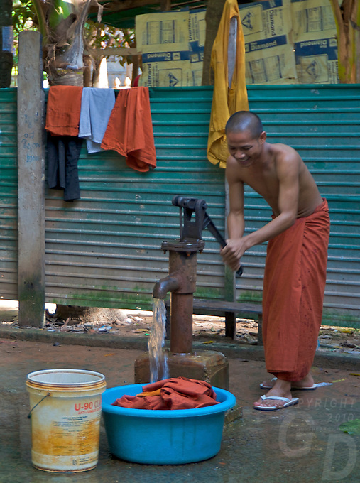Buddhist Monks pumping water for washing their Robes at a Monastery, outskirts of Siem Reap, Cambodia