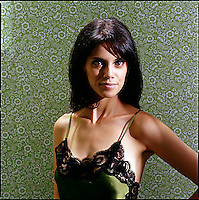 Beauty shot of woman wearing negligee against green patterned wallpaper background