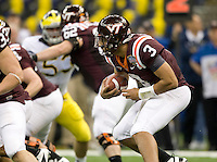 Logan Thomas of Virginia Tech runs the ball away from Michigan defender during Sugar Bowl game at Mercedes-Benz SuperDome in New Orleans, Louisiana on January 3rd, 2012.  Michigan defeated Virginia Tech, 23-20 in first overtime.