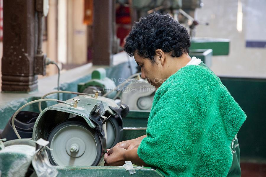 Antigua, Guatemala.  Jade Factory Workshop.  Worker Shaping Jade.