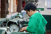 Antigua, Guatemala.  Jade Factory Workshop.  Worker Shaping Jade.