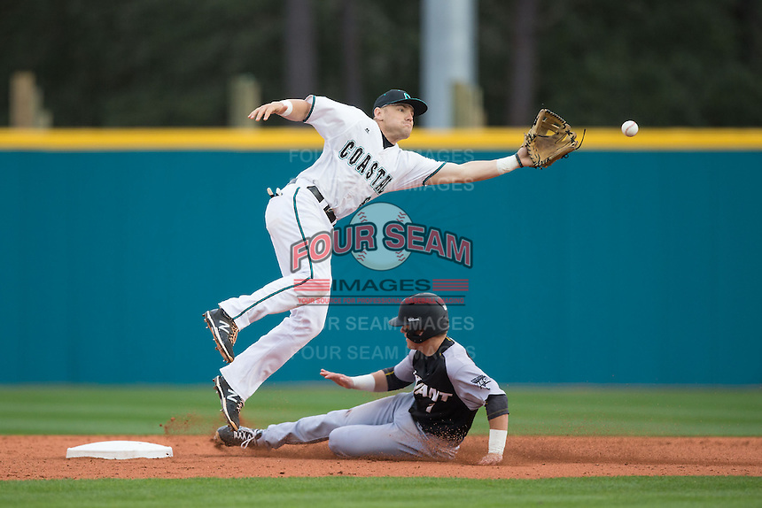 Coastal Carolina Chanticleers second baseman Connor Owings (6) leaps for a high throw as Cole Fabio (1) of the Bryant Bulldogs steals second base at Springs Brooks Stadium on March 13, 2015 in Charlotte, North Carolina.  The Chanticleers defeated the Bulldogs 7-2.  (Brian Westerholt/Four Seam Images)