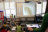 MR / Schenectady, NY. Zoller Elementary School (urban public school). Kindergarten inclusion classroom. Teacher uses digital visual presenter and digital white board to teach math lesson on place value. Students use math manipulatives (base ten blocks) and erasable worksheets to show tens and ones, then add them up to show the total. MR: AM-gKw. ID: AM-gKw. © Ellen B. Senisi.