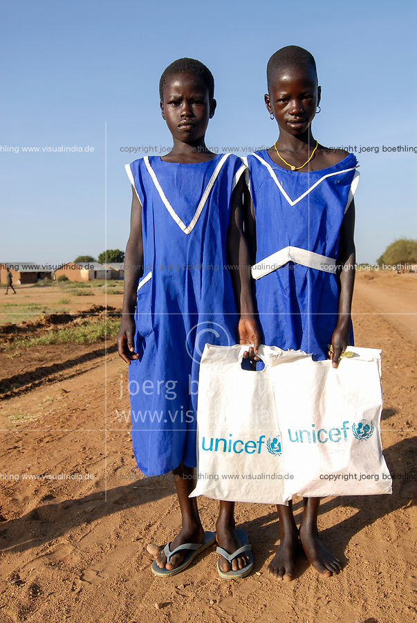 UGANDA, Karamoja, Karimojong tribe, children going home from school by walking, two girls in blue schooluniform with Unicef plastic bag for books
