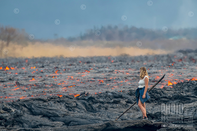 June 2018: A spectator contemplates an enormous lava river in Lower Puna, Big Island of Hawai'i. The lava river is up to 300 yards wide.