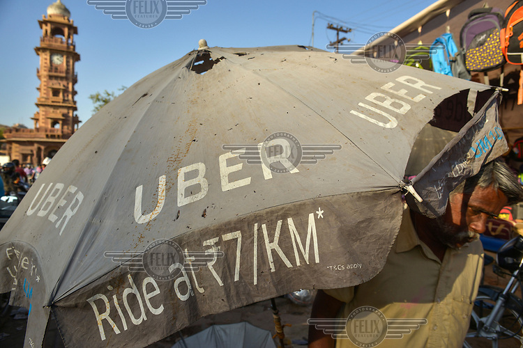A tattered umbrella advertising the Uber taxi service which is very popular across metropolitan India.