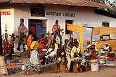 Ujiji, Tanzania. African Cinema with murals of Rambo; food market in front.
