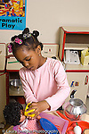 Preschool pretend play girl playing in kitchen family area with doll feeding doll vertical