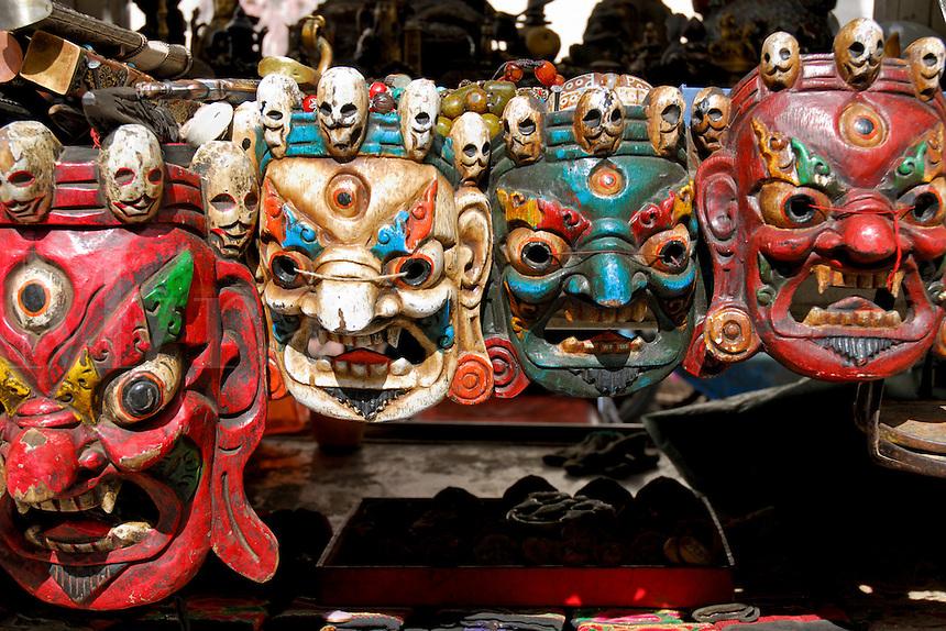 Masks of Buddhist protector deities at a market stall on the Barkhor pilgrim circuit, Lhasa, Tibet.