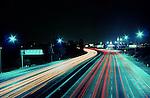 Streaking headlights on the freeway at night.