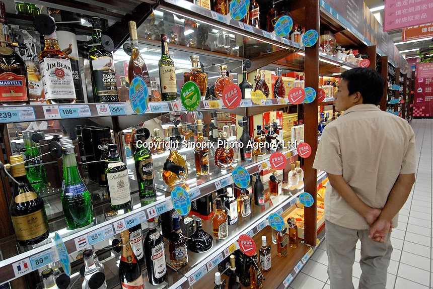 A customer passes the imported alcohol including Irish, Scottish and American whisky as well as French congac in a supermarket in Chengdu, China. A rapidly expanding middle class has created a large market for many products not previously sold in China..20 Sep 2006