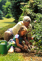 Grandfather gardening and teaching his grand daughter in yard in summer time.