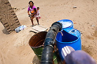 A Peruvian water distribution worker with a hose fills plastic barrels with drinking water on the dusty hillside of Pachacútec, a desert suburb of Lima, Peru, 21 January 2015. Although Latin America (as a whole) is blessed with an abundance of fresh water, having 20% of global water resources in the the Amazon Basin and the highest annual rainfall of any region in the world, an estimated 50-70 million Latin Americans (one-tenth of the continent's population) lack access to safe water and 100 million people have no access to any safe sanitation. Complicated geographical conditions (mainly on the Pacific coast), unregulated industrialization (causing environmental pollution) and massive urban poverty, combined with deep social inequality, have caused a severe water supply shortage in many Latin American regions.