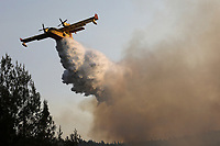 Pictured: A aeroplane douses the flames in Varibobi, Athens, Greece. Wednesday 04 August 2021<br /> Re: Forest fire in Varibobi, on the outskirts of Athens, Greece.