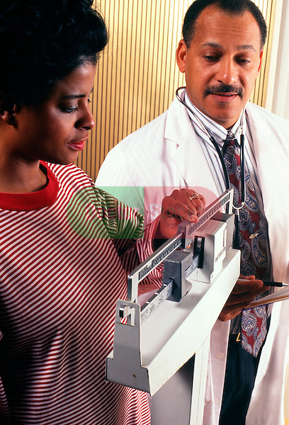 doctor watching as pregnant woman weighs herself on scale during OB/GYN visit