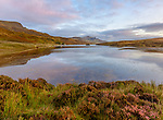 Isle of Skye, Scotland: Sunrise light and clouds reflecting in Loch Fada with heather blooming on the shoreline and the iconic Old Man of  Storr in the distance.