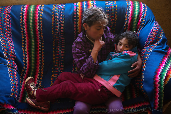 Tahis Bionica Palma Carhuaricra, 7, is seen with her elder sister, Shirley Palma Carhuaricra, inside their home in Paragsha neighborhood of Cerro de Pasco on June 26, 2013. In 2007 Tahis Bionica tested with 66.02% lead poisoning in her blood, one of the highest levels recorded in Cerro de Pasco. She started having seizures when she was 6 months old, and her mother said she has had more than one hundred. Tahis Bionica has severe disabilities and is unable to talk or eat normal food. She stays at home while her sisters attend school.