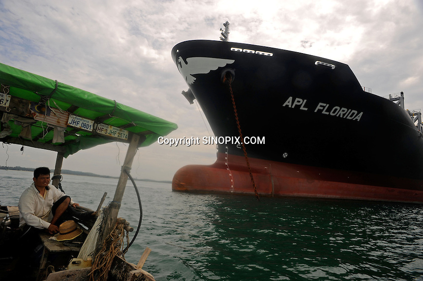Two container ships are tied together several kilometers out to see off the coast of Sunghai Rengit, southern Malaysia. There are hundreds of container ships and oil tankers moored in a 30 km stretch in international waters where it is cheap to moor the boats.