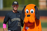 "Bruce Steel (17) of the Wake Forest Demon Deacons poses with ""Rover"" following the ceremonial first pitch on ""Bark in the Park"" day prior to the game against the Florida State Seminoles at David F. Couch Ballpark on April 16, 2016 in Winston-Salem, North Carolina.  The Seminoles defeated the Demon Deacons 13-8.  (Brian Westerholt/Four Seam Images)"