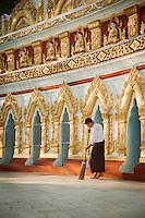 A groundskeeper sweeps outside the U Min Thone Sel pagoda in Sagaing, Myanmar