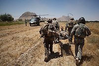 US Army soldiers carry an injured soldier onto a waiting medevac helicopter from Charlie Company, Sixth Battalion, 101st Aviation Regiment near Kandahar.