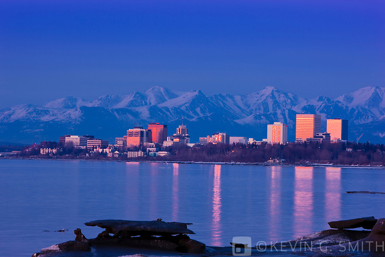 Anchorage Skyline reflected in the waters of Knik Arm at sunset as seen in this photo from Earthquake park, late winter, Southcentral Alaska, USA.
