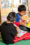 Education preschool 3-4 year olds two boys sitting separately but near each other both looking at picture books