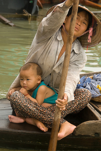 Mother and Child selling food in floating Vietnamese village near Siem Reap, Cambodia. The mother is wearing the traditional Vietnamese conical hat.  The Vietnamese floating villagers on branches of Lake Tonie Sap, Cambodia are a unique nomadic community. With permission from the Cambodian government, they have built an entire floating community of houseboats, churches, clinics, shops and community centers on the river near Siem Reap, Cambodia.   As the water retreats, and the rainy season approaches; the entire village moves further inland to take shelter along the river banks.  The villagers rely on sales of fruits and soft drinks to the many tourists who have come by boat to see firsthand the hardships of life on a floating village.