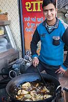 India, Dehradun.  Young Man Cooking Samosas.