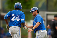 GCL Blue Jays third baseman Joseph Reyes (24) is congratulated by manager Luis Hurtado (31) as he rounds third base after hitting a home run in the top of the ninth inning during a game against the GCL Phillies East on August 10, 2018 at Carpenter Complex in Clearwater, Florida.  GCL Blue Jays defeated GCL Phillies East 8-3.  (Mike Janes/Four Seam Images)