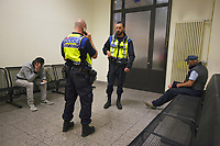 Switzerland. Canton Ticino. Chiasso. Railway station. Two police officers from TPO (Transport Police) are controlling the identities of two men seated let at night in the waiting room of the train station. The young man (L) is from Albania and is waited for the morning train to go to Italy. The other man (R) is an one-legged homeless man from Italy who comes at night to sleep in the waiting room for safety reason. TPO (Transport Police) is the Swiss Federal Railways Police. Swiss Federal Railways (German: Schweizerische Bundesbahnen (SBB), French: Chemins de fer fédéraux suisses (CFF), Italian: Ferrovie federali svizzere (FFS)) is the national railway company of Switzerland. It is usually referred to by the initials of its German, French and Italian names, as SBB CFF FFS. TILO (Treni Regionali Ticino Lombardia) creates efficient train connections between the towns in the canton Ticino.10.06.2017 © 2017 Didier Ruef
