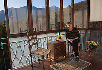 Switzerland. Canton Ticino. Sala. Elsy (Elsa) Hofer Ferrari Ramuz is 86 years old. She seats on a chair in the balcony of her home. Plastic flowers for decoration. Roses and sunflower. Helianthus or sunflower is a genus of plants comprising about 70 species in the family Asteraceae. Elsy Hofer Ferrari Ramuz is the niece of Charles-Ferdinand Ramuz (September 24, 1878 – May 23, 1947) who was a French-speaking Swiss writer. 14.11.2017 © 2017 Didier Ruef