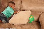 Baby boy 10 months old at home looking for and finding toy ball hidden under cushion