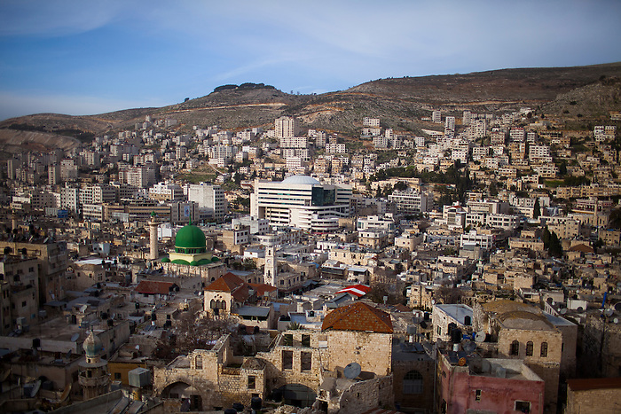 Jan 2013, Nablus city center: in the foreground, the old city, which is still standing despite the heavy damages endured during the two intifadas. In the middle, a giant mall center and multiplex cinema. In the background, the newer part of the city with towers. Like every developing city in the world, buildings are built always higher: but in Palestine, the height of estate is even more pushed by the land prize: in the 84% (B and C zones) of the West Bank, building requires permission from the Israeli army, almost never granted. Therefore the A zones (such as Nablus city) are the only part of the territory left for serious estate project, which prizes raise disproportionally every year due to the demographic pressure and the impossible territorial expansion.