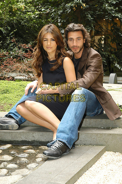 "MONICA CRUZ & DANIELE LIOTTI.Photocall for the film ""L'Inchiesta"" in Rome, Italy..March 29th, 2007.full length jacket brown beard facial hair black dress arms around waist sitting jeans denim .CAP/CAV.©Luca Cavallari/Capital Pictures"