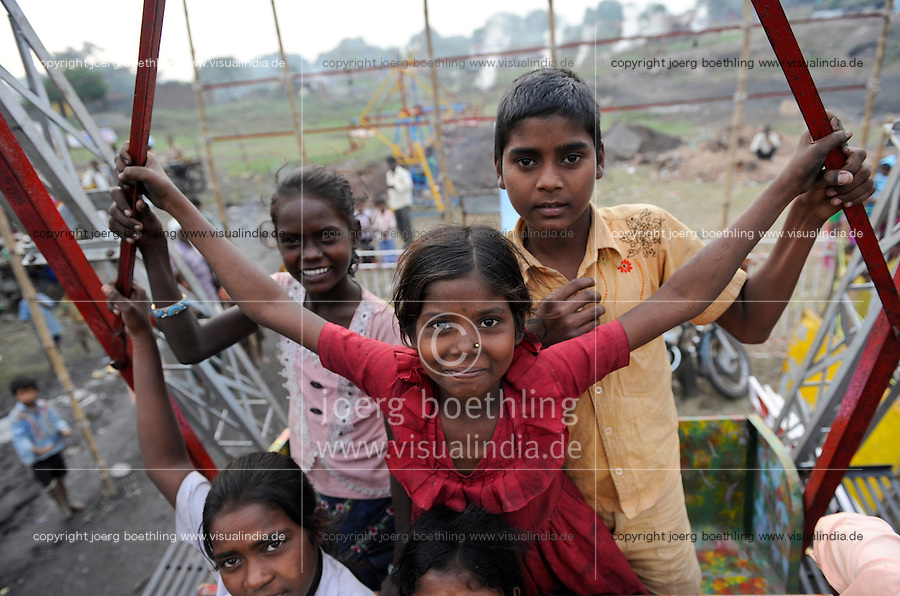 INDIA Jharkhand Dhanbad Jharia , girl Sonia in swing at fair , background smoke of burning underground coal seams, usually she works as coal picker / INDIEN Kohlerevier Dhanbad / Jharia , Maedchen Sonia 8 Jahre in einer Schaukel auf einem Jahrmarkt vor brennenden Kohlefloezen, Sonia sammelt Kohle in Abraumhalden um Geld fuer die Familie zu verdienen