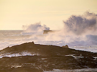 At sunset, high surf creates powerful waves that crash against the rocky coastline near an OTEC (Ocean Thermal Energy Conversion) facility on the Big Island of Hawai'i.