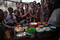 Inmates in Pademba Central Prison queue up for their meagre daily ration of rice. Malnutrition and dehydration are common among the inmates who receive an insufficient supply of water and food..