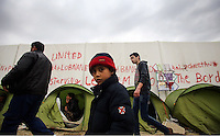 Pictured: A young boy and adult migrants at the Idomeni camp Monday 29 February 2016<br /> Re: A crowd of migrants has burst through a barbed-wire fence on the FYRO Macedonia-Greece border using a steel pole as a battering ram.<br /> TV footage showed migrants pushing against the fence at Idomeni, ripping away barbed wire, as FYRO Macedonian police let off tear gas to force them away.<br /> A section of fence was smashed open with the battering ram. It is not clear how many migrants got through.<br /> Many of those trying to reach northern Europe are Syrian and Iraqi refugees.<br /> About 6,500 people are stuck on the Greek side of the border, as FYRO Macedonia is letting very few in. Many have been camping in squalid conditions for a week or more, with little food or medical help.