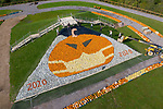 FRIDAY 9TH OCTOBER 2020<br /> <br /> Pictured: Workers at Sunnyfields Farm in Totton, Hants form a socially distanced line as they toss pumpkins to create a giant artwork of a pumpkin donning a facemask, made up of over 5,000 of the vegetables which goes on display to the public for the first time tomorrow. <br /> <br /> © Jordan Pettitt/Solent News & Photo Agency<br /> UK +44 (0) 2380 458800