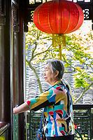 Yangzhou, Jiangsu, China.  Woman Admiring Courtyard of the Ho Family House and Garden.